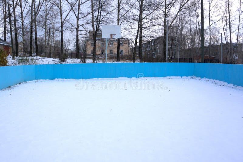 一个室外滑冰的溜冰场和曲棍球网与高霜盖了树在背景中在冬天风景 免版税库存图片