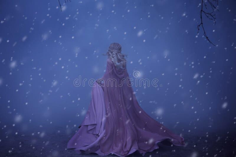 一个害怕女孩金发碧眼的女人在大雾跑 在矮子、一件豪华桃红色礼服有一列长的火车的和雨衣上 那里 免版税库存照片