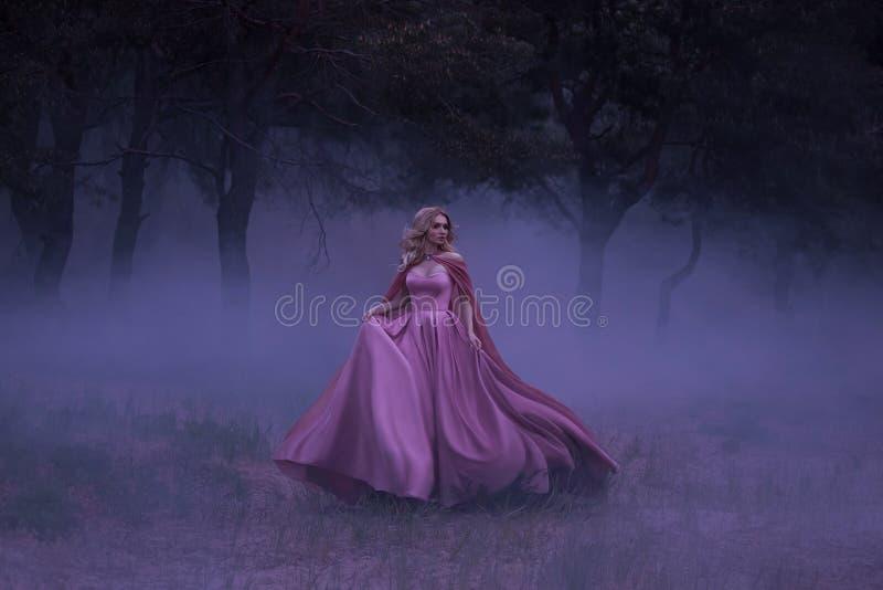 一个害怕女孩金发碧眼的女人跑远离盖了大雾的森林 在矮子,有a的一件豪华桃红色礼服 免版税库存图片