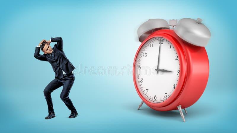 一个害怕的商人掩藏远离站立在蓝色背景的一个巨型红色闹钟 免版税库存照片