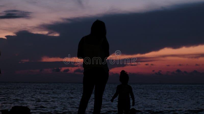 一个家庭母亲的剪影有婴孩步行的在日落海 库存照片