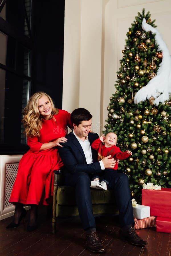 一个家庭的画象在圣诞树背景的 妈妈、爸爸和一个一岁的男婴 库存照片