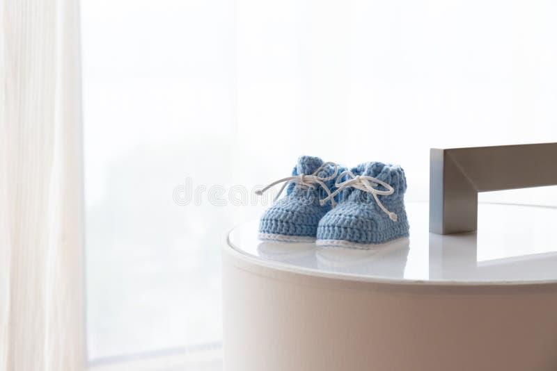 一个对反对由后面照的窗口的蓝色婴儿鞋子 免版税库存照片