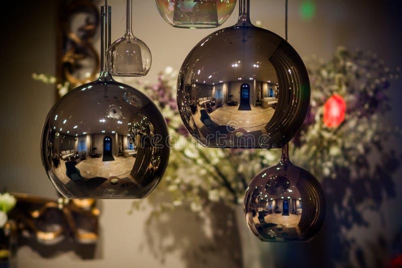 一个对围绕金黄室内枝形吊灯的现代镜子 泡影金属金与选择聚焦的树荫垂饰 图库摄影