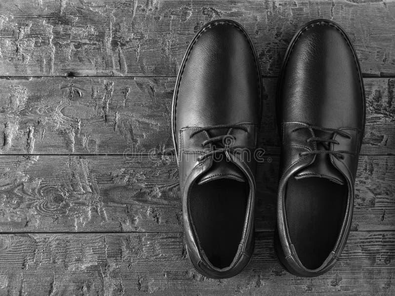 一个对在一个黑木地板上的经典黑人皮革人的鞋子 r 库存图片