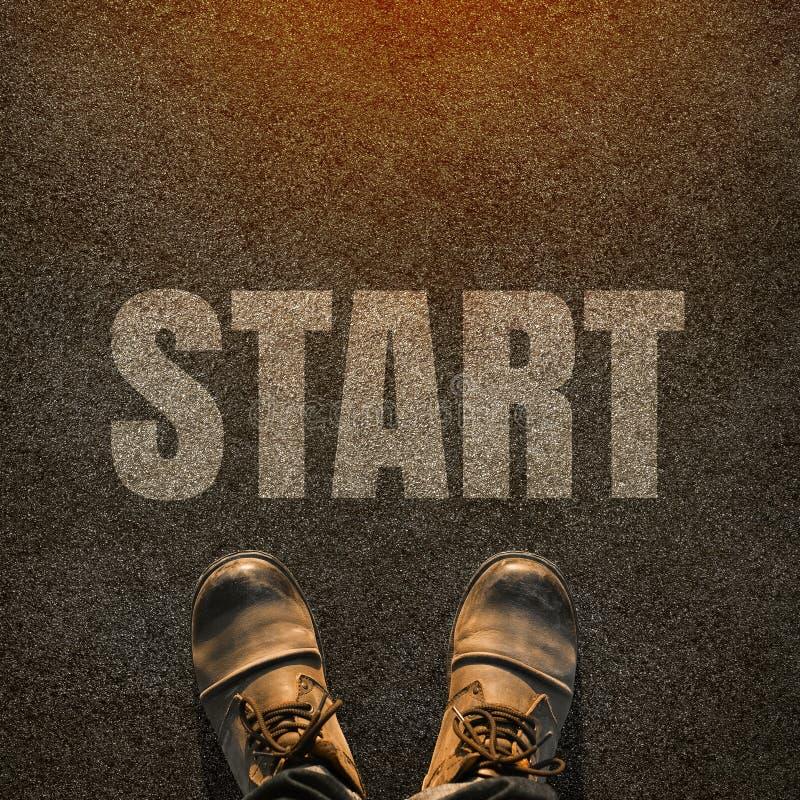 一个对在柏油碎石地面路的脚有词sta的白色印刷品的 图库摄影
