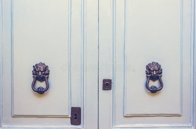 一个对在浅兰的门的老金属狮子头敲门人 库存图片