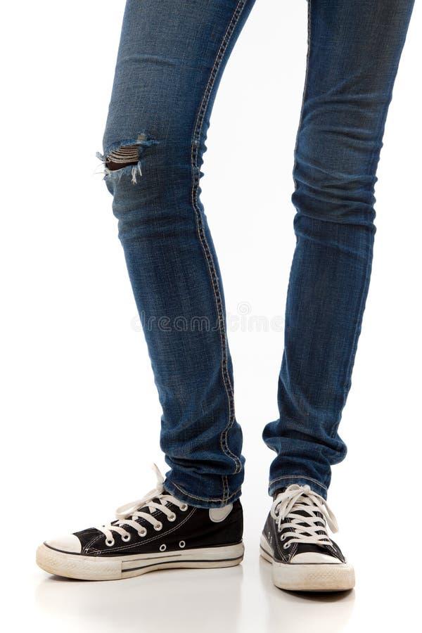 有牛仔裤和减速火箭的黑运动鞋的腿在白色背景 库存图片