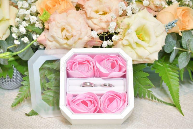 一个对在许多花围拢的箱子的结婚戒指 免版税库存照片