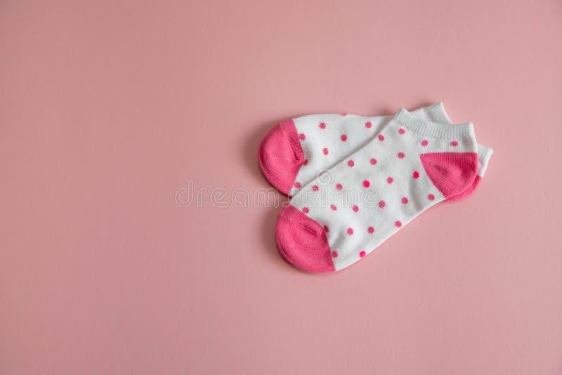 一个对孩子有桃红色袜子的和脚跟的白色袜子,有桃红色小点的,在桃红色背景 女孩的袜子 免版税库存照片
