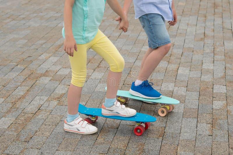 一个对孩子,男孩和女孩,在体育板,特写镜头站立,在石路面 库存照片