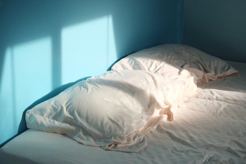 一个对有一个床单的起皱纹的枕头在蓝色屋子 库存照片