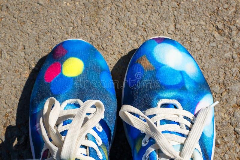 一个对有白色鞋带的蓝色纺织品运动鞋在沥青背景在一好日子 E 图库摄影