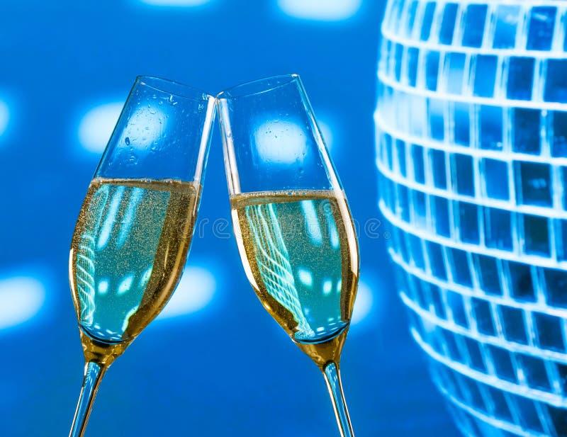 一个对有金黄泡影的香槟槽在闪耀的蓝色迪斯科球背景做欢呼 库存图片