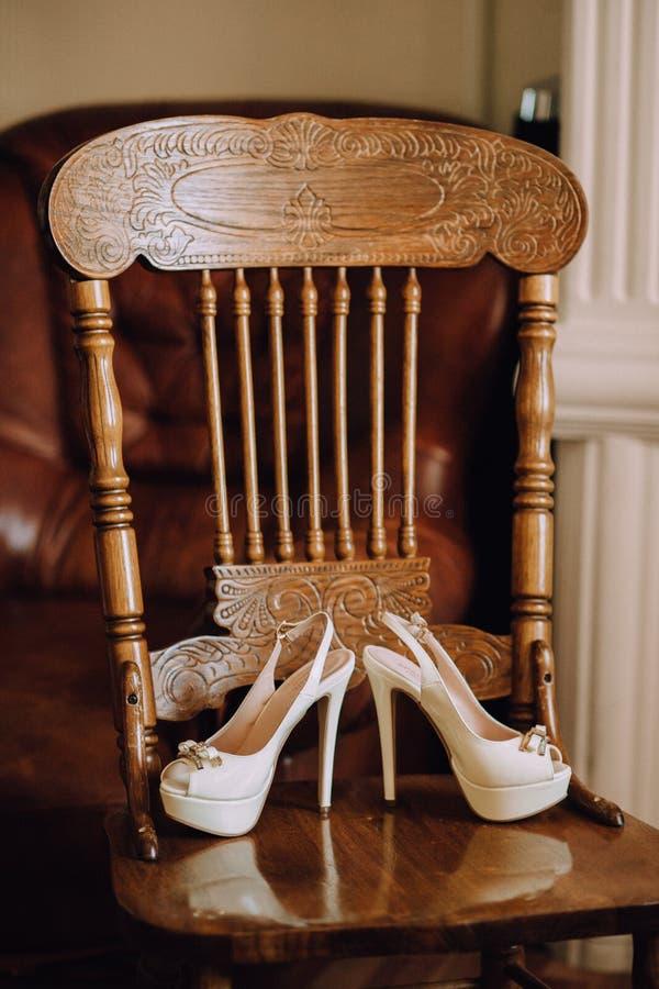 一个对有高跟鞋的美丽的白色婚礼鞋子在一把木葡萄酒椅子站立 库存图片