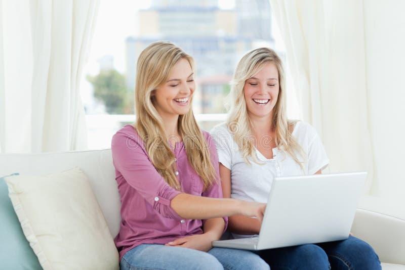一个对笑的妇女坐有一台膝上型计算机的长沙发在h 免版税库存照片