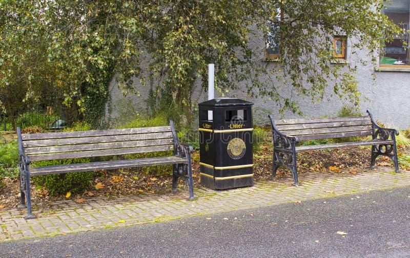 一个对被毁坏的公园长椅和一个市议会垃圾桶在路旁在Edenderry小磨房村庄在南B 库存图片