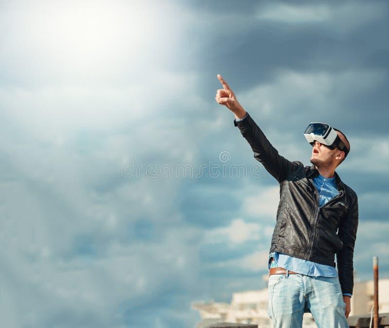 戴一个对VR眼镜的确信的年轻人站立在屋顶大厦的城市上有激动的蓝天背景 免版税库存照片