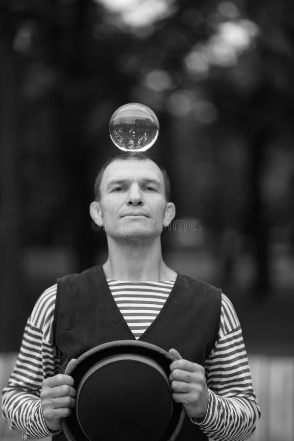 一个小丑人拿着一个透明不可思议的球 免版税库存照片