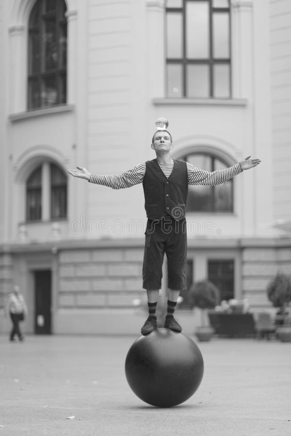 一个小丑人拿着在他的头的一个透明不可思议的球 库存图片