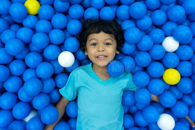 一个小亚裔男孩使用与很多蓝色和黄色球 库存图片