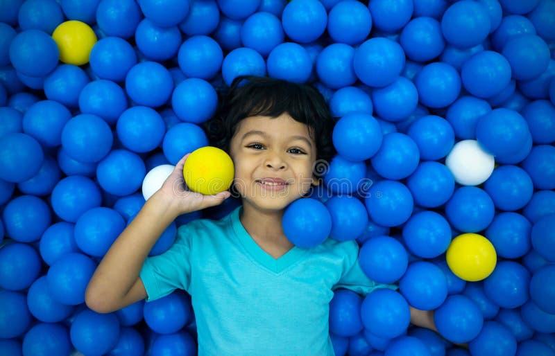 一个小亚裔男孩使用与很多蓝色和黄色球 免版税库存照片