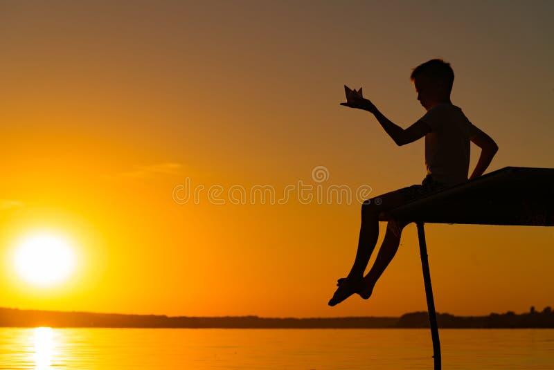 一个小人在他的手上坐桥梁并且举行纸船origami在晚上在日落 男孩使用与他的 库存图片