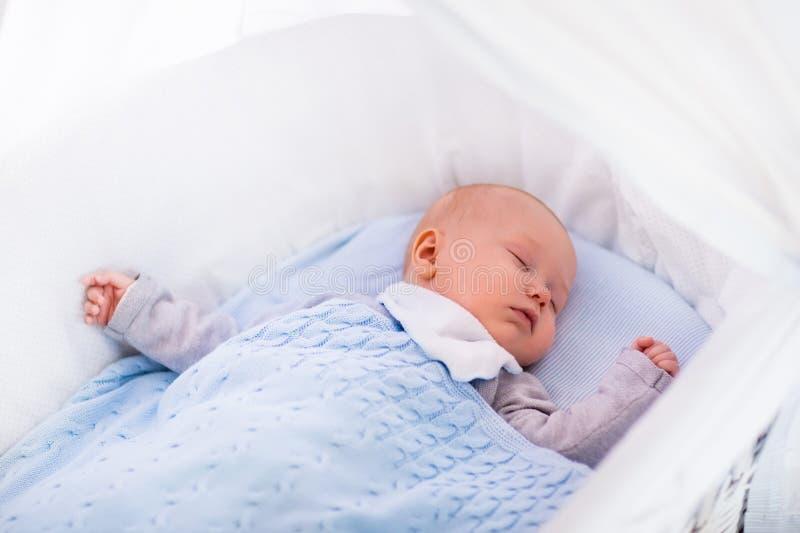 一个小儿床的男婴在被编织的毯子下 免版税图库摄影