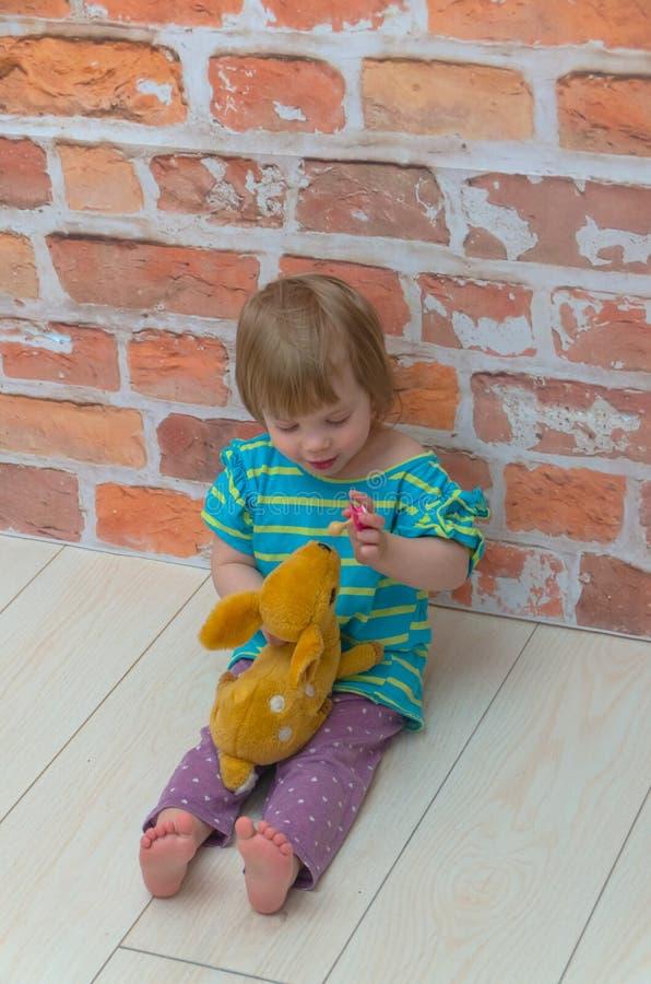 一个小女孩、一个孩子有安慰者的和一头玩具驯鹿在bac 库存图片
