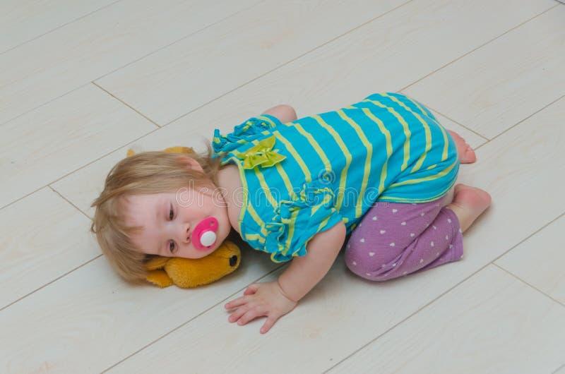 一个小女孩、一个孩子有安慰者的和玩具鹿 库存图片