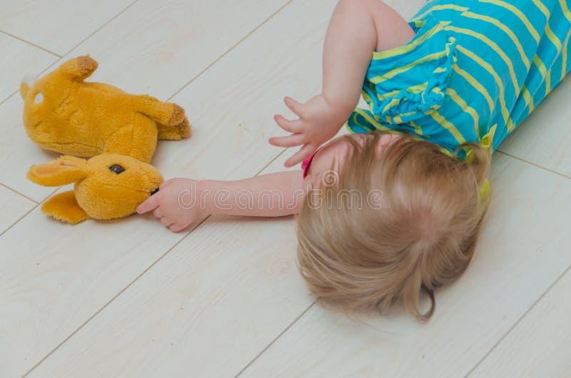 一个小女孩、一个孩子有安慰者的和玩具鹿 免版税库存图片