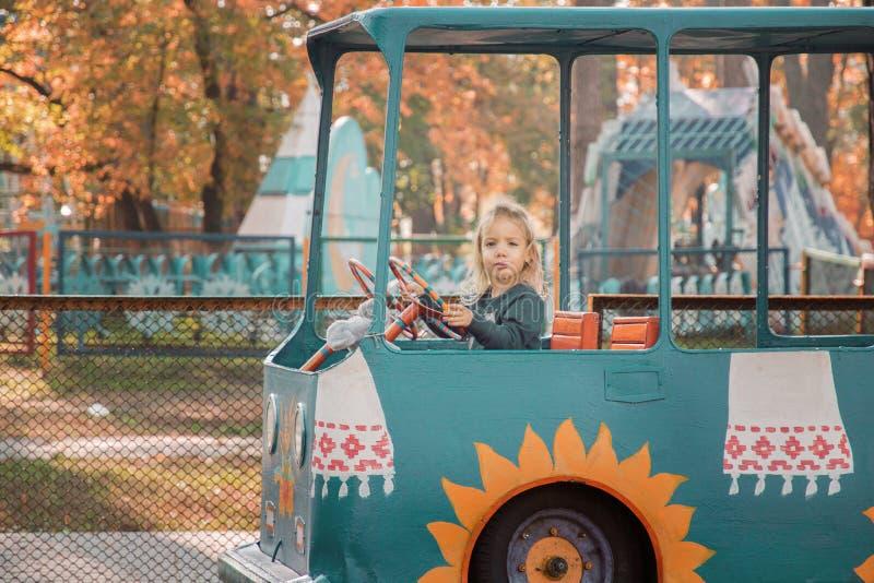一个小女孩乘坐在吸引力的一辆汽车 图库摄影