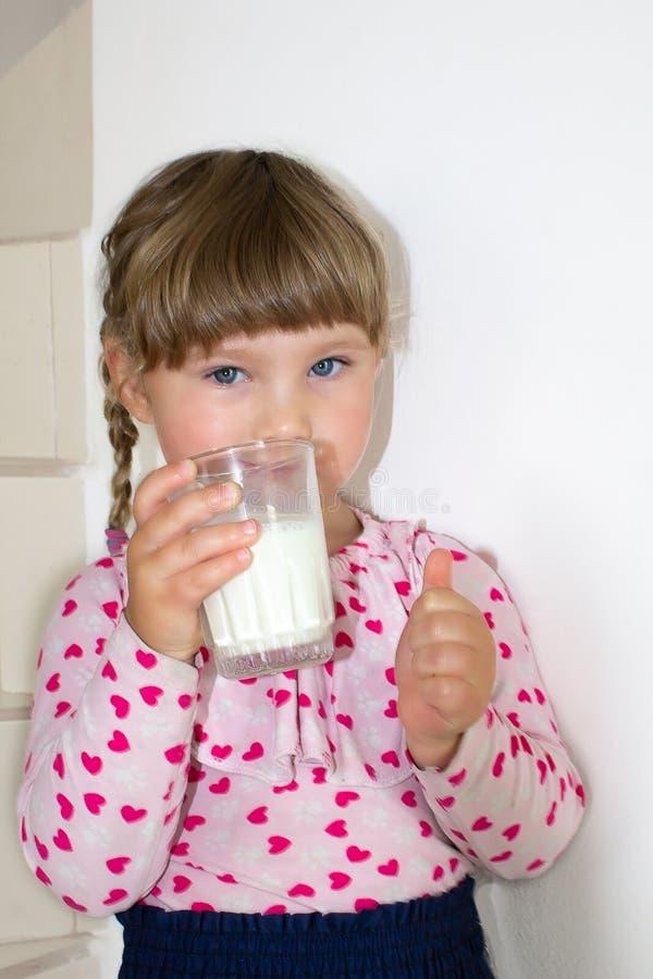 一个小女孩喝牛奶并且显示赞许、牛奶的孩子的好处和钙 免版税库存图片
