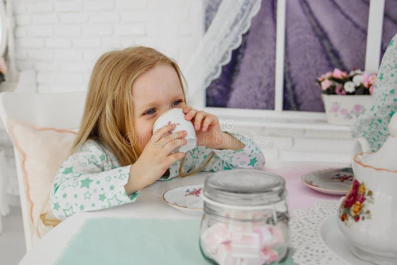 一个小女孩喝茶,拿着杯子 由桌坐 免版税库存图片