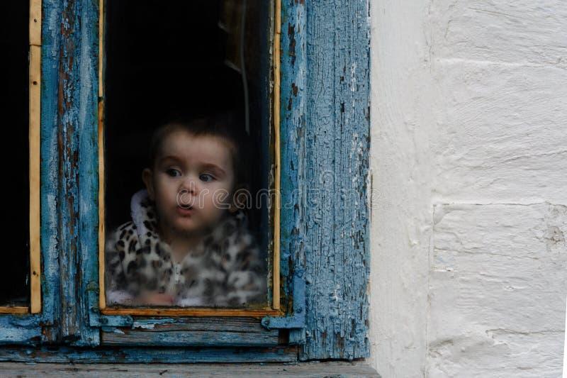 一个小女孩在一个老小屋坐油漆退色的窗口 免版税库存图片