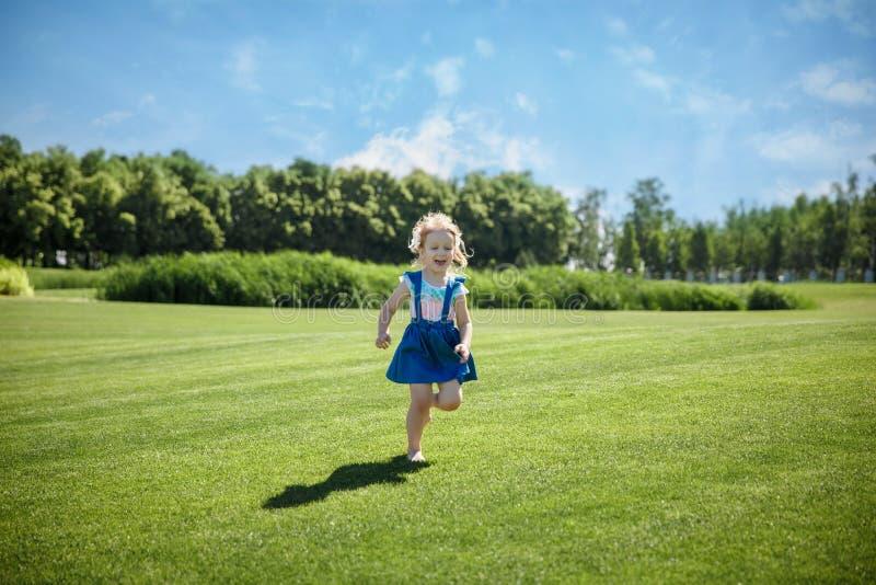 一个小女孩在公园跑 免版税库存照片