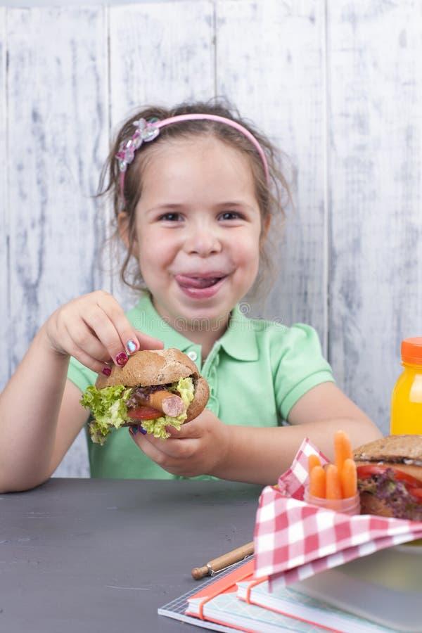 一个小女孩在学校吃着她的午餐 午餐女小学生 敬酒和和新鲜的汁液和沙拉一顿健康晚餐的 自由 免版税库存图片