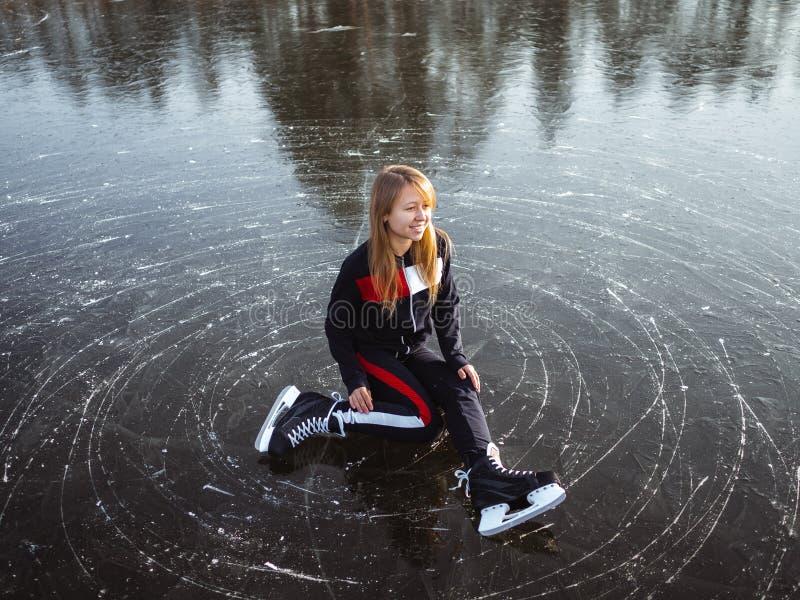 一个小女孩坐在湖边溜冰的画像 库存照片