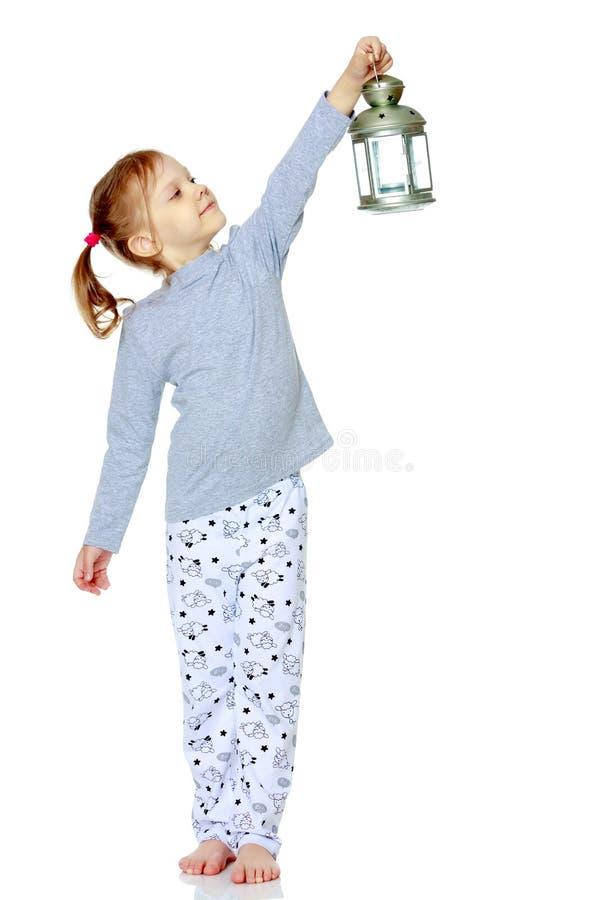 一个小女孩拿着一盏灯 免版税库存照片