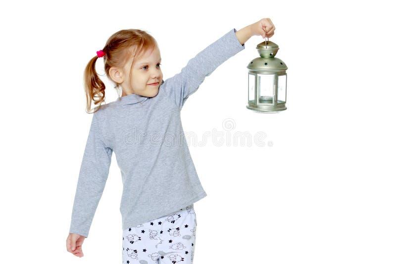一个小女孩拿着一盏灯 免版税库存图片