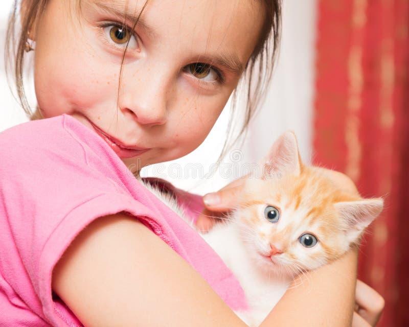 一个小女孩拿着在她的胳膊和拥抱的一只小猫 免版税库存照片