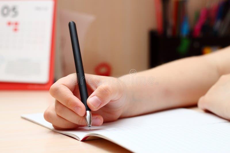 一个小女孩拿着笔,在笔记本上写字。一个小女孩拿着笔,在笔记本上写字。手的特写 免版税图库摄影