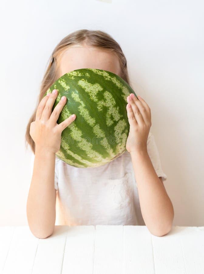 一个小女孩是西瓜,鸦声,笑,幽默,情感,吃西瓜 库存照片