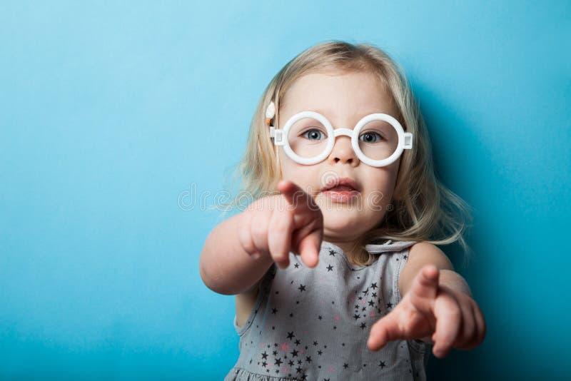 一个小女孩用手指和手指点着 玩具时尚眼镜 库存照片