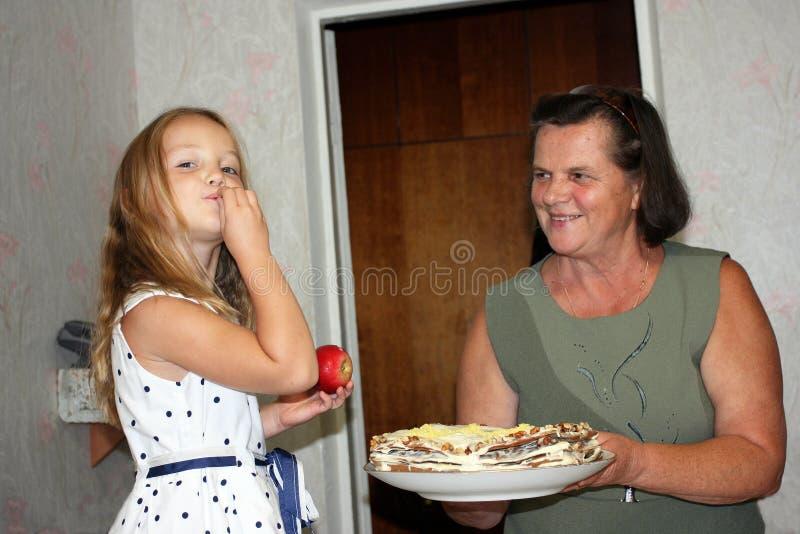 一个小女孩由她的从板材的手品尝蛋糕 免版税库存照片