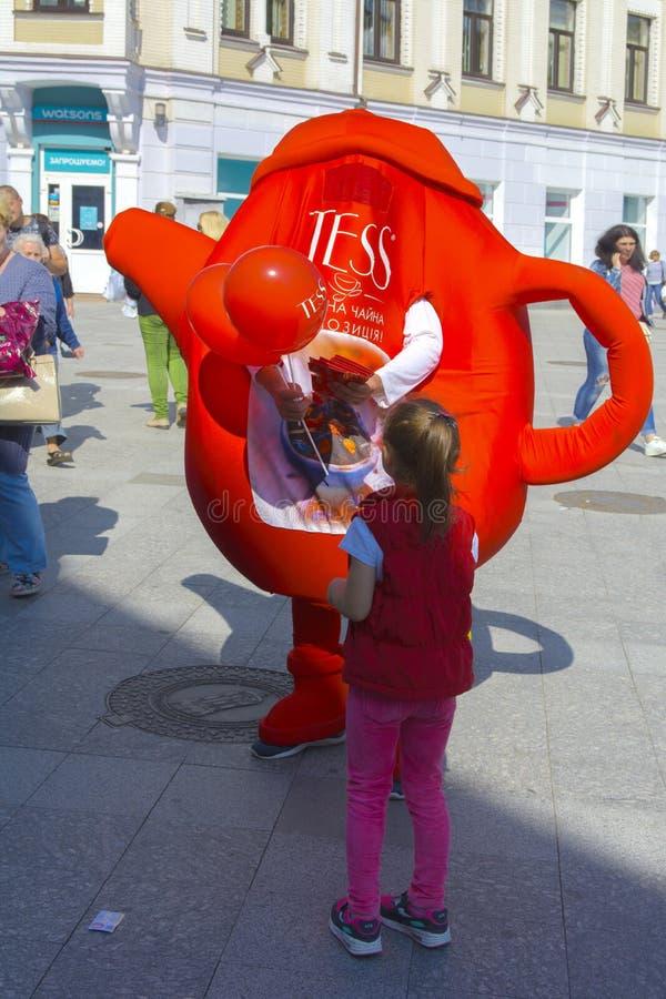 一个小女孩由手拿着一个可膨胀的广告玩具 免版税图库摄影