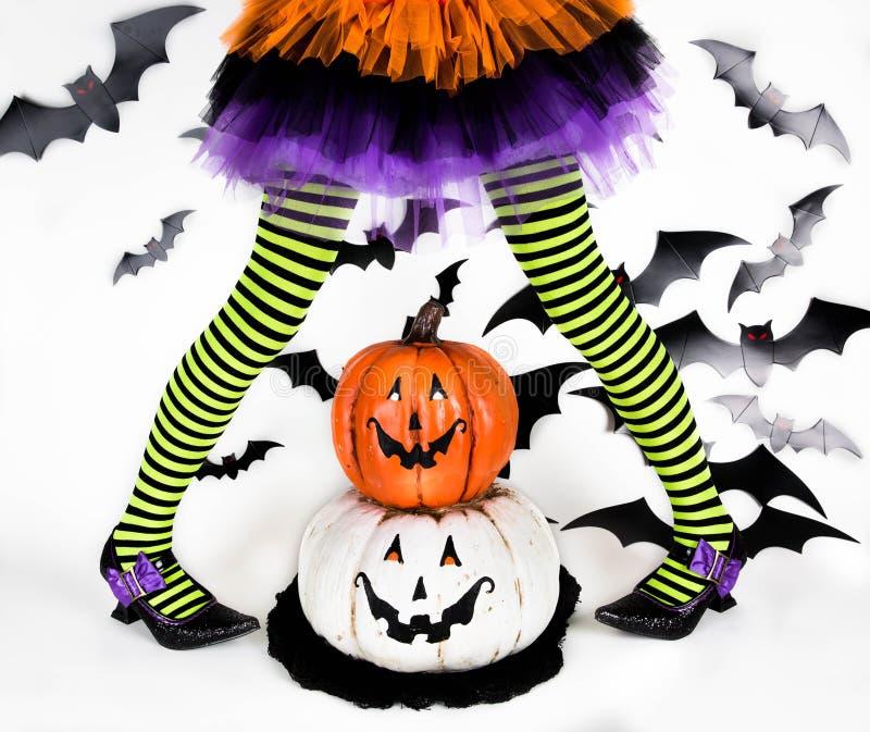 一个小女孩的滑稽的绿色黑镶边腿有一个巫婆的万圣夜服装的有巫婆鞋子和兴高采烈的万圣夜南瓜的 库存照片