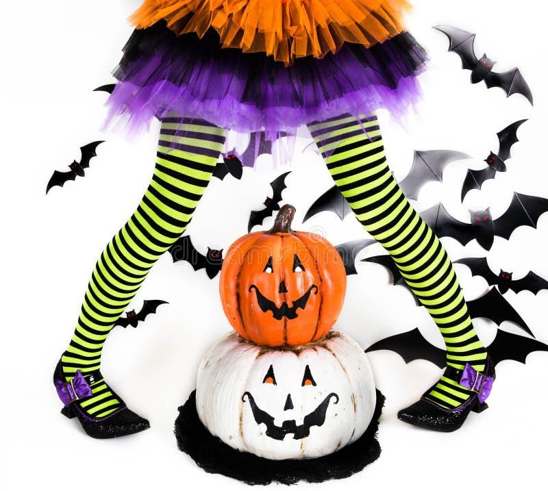 一个小女孩的滑稽的绿色黑镶边腿有一个巫婆的万圣夜服装的有巫婆鞋子和兴高采烈的万圣夜南瓜的 库存图片