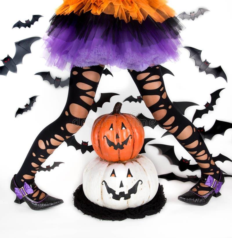 一个小女孩的滑稽的黑腿有一个巫婆的万圣夜服装的有巫婆鞋子和兴高采烈的万圣夜南瓜的 免版税库存图片