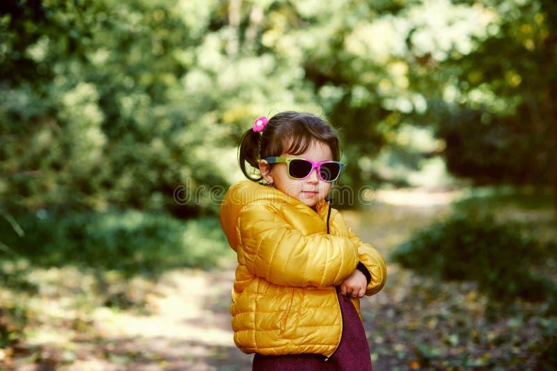 一个小女孩的画象步行的在城市公园在秋天 免版税库存照片
